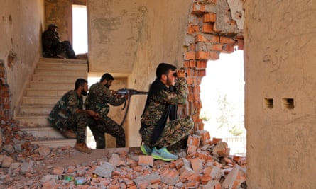 Kurdish fighters take up positions in a damaged building in Hasaka.