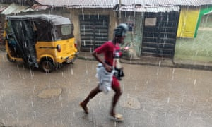 A girl runs in rain at Agege area of Lagos, Nigeria on Tuesday 23 July 2019