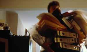 A man holding a large stack of paper files with some of them falling off