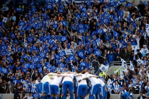 Brighton players huddle before kick off with fans celebrating the club's promotion to the Premier League