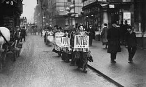Suffragettes walk along a London street wearing sandwich boards demanding that women be given the vote, 1912.