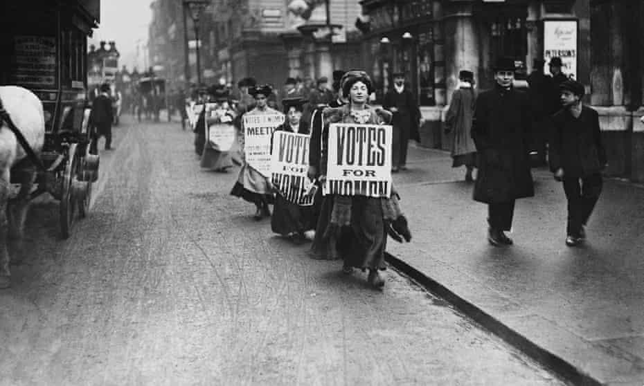 Suffragettes walk along a London street wearing sandwich boards demanding that women be given the vote. 1912.