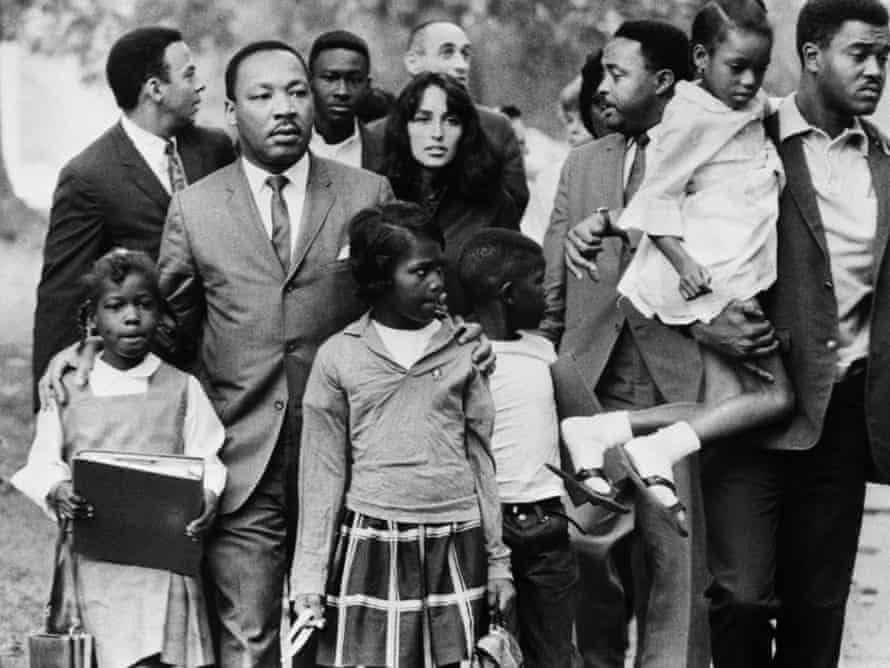 Dr Martin Luther King is shown leading a group of black children to their newly integrated school in Grenada, Mississippi, escorted by folk singer Joan Baez and two aides.