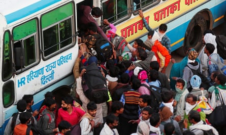 A crowd of people surrounding the entrance to a bus with someone on board trying to reach down to help someone in the crowd up