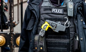 A police officer carrying a Taser electronic weapon.