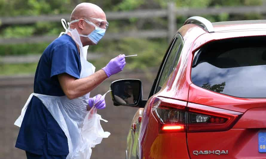 A medical professional tests an NHS worker for Covid-19 at a drive-through testing centre.