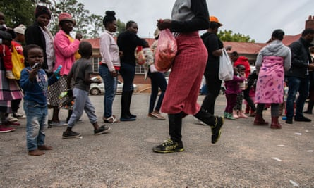 People queue for food parcels at an animal welfare clinic in Durban Deep, Johannesburg