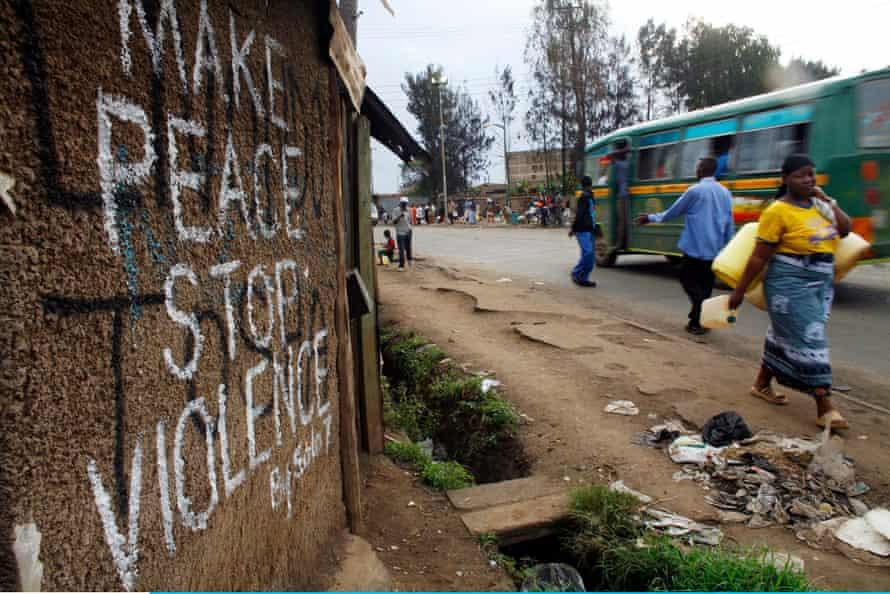 A Kenyan woman walks past a sign calling for peace in the Kibera slums, Nairobi, Kenya