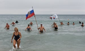Crimean people wave a Russian national flag