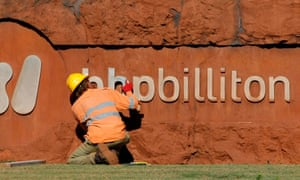 A man mends a sign at the entrance to BHP Billiton's iron ore loading facility in Port Hedland