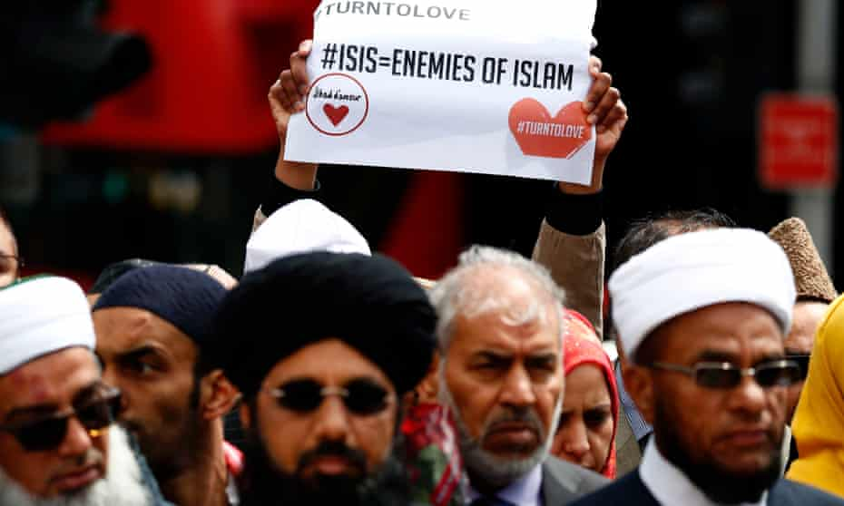 A person holds a placard during a gathering of representatives of the Muslim south of London Bridge in London on 7 June 2017