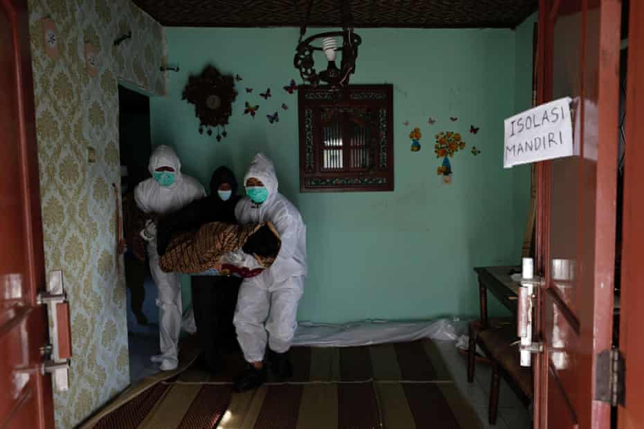 Kerabat yang mengenakan alat pelindung diri menemukan mayat Yoyo Satia, 64 tahun, meninggal di kuil saat diasingkan di rumahnya di Bogor, Jawa Barat, Indonesia.
