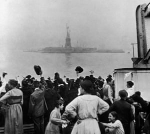 A group of immigrants travelling aboard a ship celebrate as they catch their first glimpse of the Statue of Liberty and Ellis Island in New York Harbour.