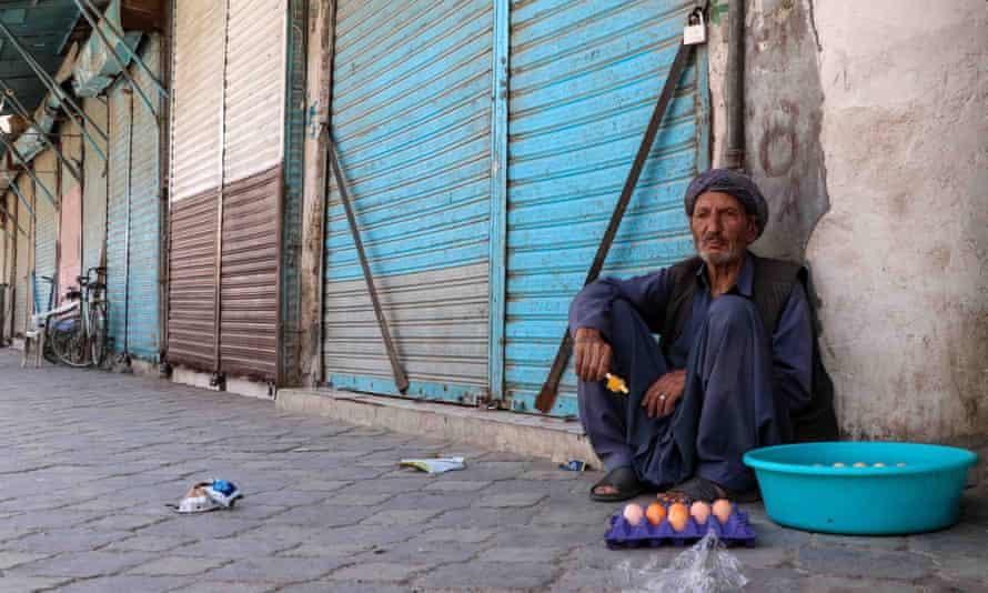An Afghan man sells boiled eggs beside closed market stalls in Kandahar