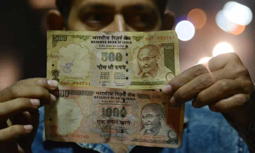 A man holds a 500 and 1,000 Indian rupee note, both of which will no longer be legal tender from midnight.