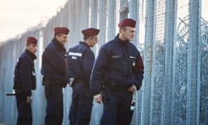 Hungarian police officers patrol the temporary border fence on the Hungarian-Serbian border near Roszke, 180km southeast of Budapest.