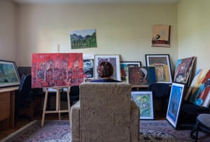 Drita sits in a chair surrounded by pictures in Medica Kosova's art therapy room