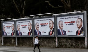 A woman walks past AKP billboards in Istanbull thanking voters featuring Erdoğan and mayoral candidate Binali Yıldırım