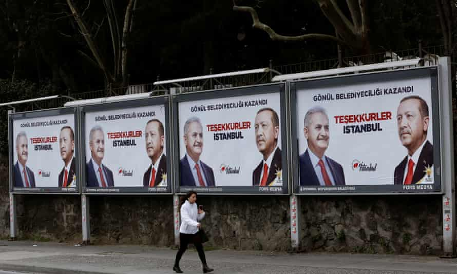 A woman walks past AKP billboards in Istanbull thanking voters featuring Erdoğan and mayoral candidate Binali Yıldırım