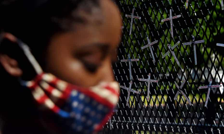 A demonstrator next to a fence bearing names of black people killed by police, Washington DC, June 2020.