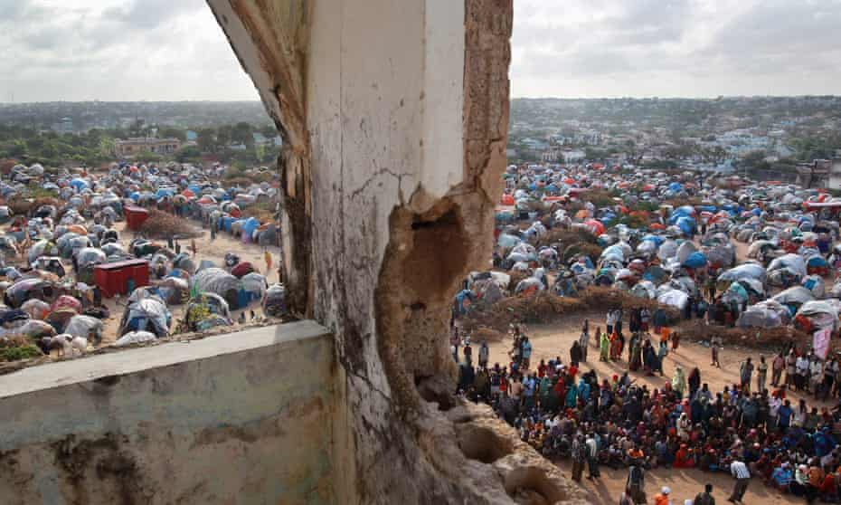 People wait for cooked food at a feeding center at a camp for Somalis displaced by drought and famine