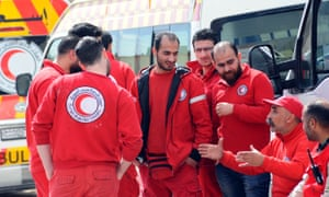 Syrian Red Crescent workers wait to evacuate wounded civilians from the fighting in eastern Ghouta.