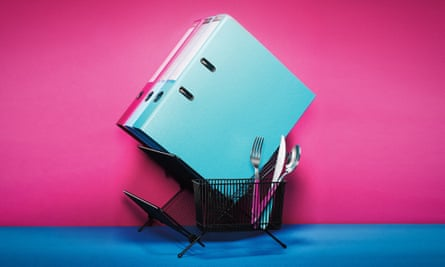 Files next to cutlery in a kitchen sink drainer against pink and blue background