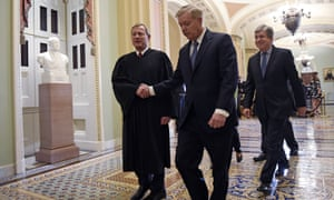 Lindsey Graham, center, shakes hands with John Roberts, left, as they walk out of the Senate chamber on Capitol Hill in Washington DC, on 5 February.