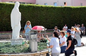 Pilgrims pray at the statue of Our Lady of Medjugorje to mark the 40th anniversary of the alleged appearance of the Virgin Mary to local shepherds in the hills surrounding the village in Medjugorje, Bosnia and Herzegovina