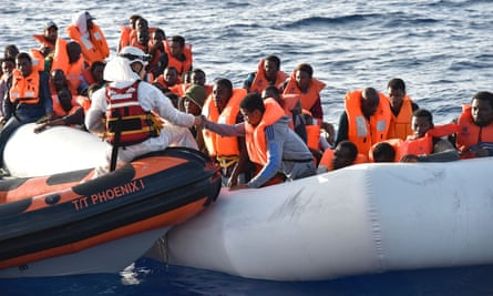 People are helped into a small rescue boat in the Mediterranean Sea