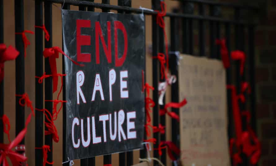 A placard saying 'End Rape Culture' attached to the fence outside a school.