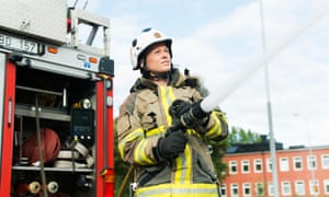 Female firefighter using fire hose next to truck