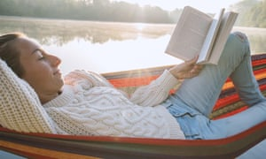 Young woman relaxing on hammock with a book