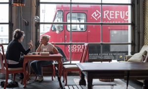 Katy Long talks with the founder of Clarkston's Refuge Coffee. Beverages are made and served by hired refugees inside the coffee truck parked outside.