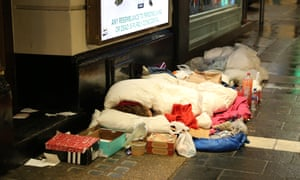 Homeless person in sleeping bag on street, surrounded by belongings