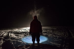 A Canadian Ranger, illuminated by a snowmobile and his headlamp during a snowstorm, helps pull a net using under-ice fishing techniques for Arctic char during a patrol on King William Island, Nunavut. Canadian Rangers are a volunteer, community-based military unit. In the Arctic they are mostly Inuit.