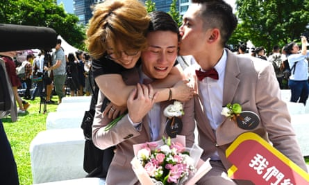 An emotional Shane Lin (C) is comforted by his new husband Marc Yuan (R) and a friend during a wedding ceremony in Shinyi district in Taipei.