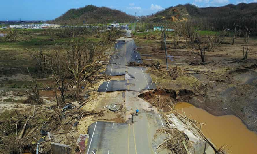 A man rides his bicycle through a damaged road, following the passage of Hurricane Maria.