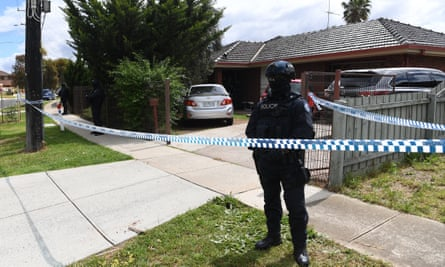 A Victorian police officer stands outside a property located in Werribee, Melbourne