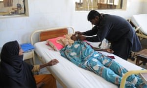 Woman receives treatment at a hospital in Punjab province, Pakistan, after eating contaminated sweets