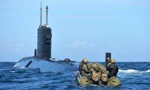 A small boat with SBS soldiers approaches a partially submerged submarine.