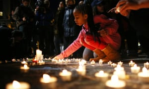 A young girl lights a candle at the Place de la Bourse in Brussels on 22 March, following the terror attacks in the city
