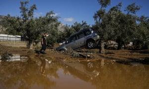 A car moved by flood water after storms in Kineta, Greece