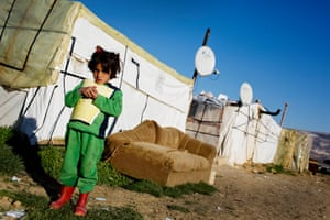 A girl holds a schoolbook outside the shelter she lives in with her family in Zahle