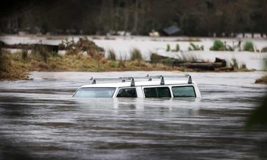 A vehicle is submerged in the Kumeu river as heavy rain causes extensive flooding and destruction in Auckland, New Zealand.