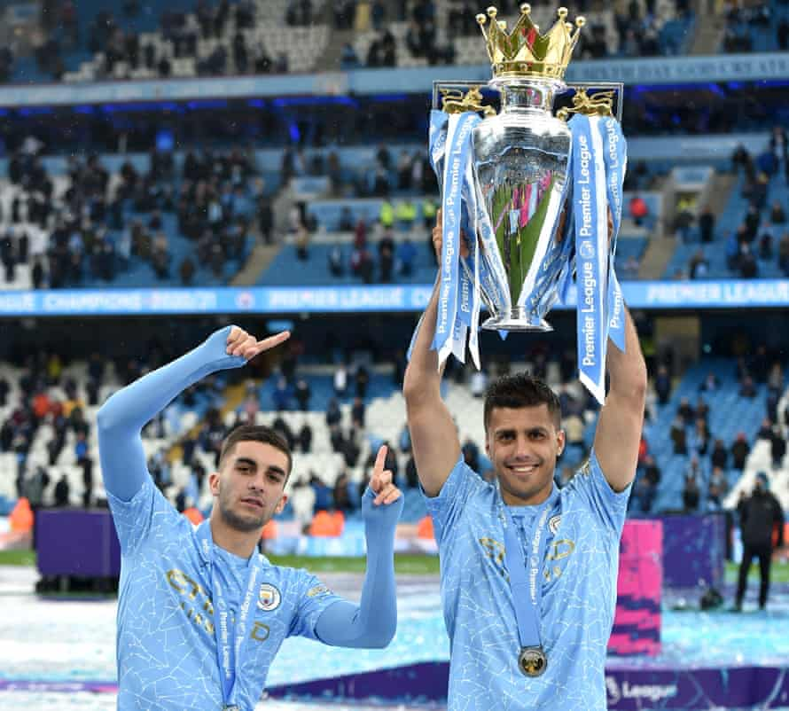 Rodri lifts the Premier League trophy alongside Ferran Torres, one of three of his Manchester City teammates in the Spain squad.