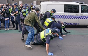 Police officers detain a man as protesters gather outside Parliament House in Melbourne.