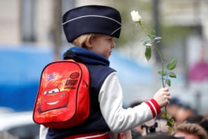 Paris, France. A young boy wearing a police cap attends a ceremony commemorating police officer Xavier Jugele, one of three people killed on the Champs-Élysées in a 2017 terrorist attack