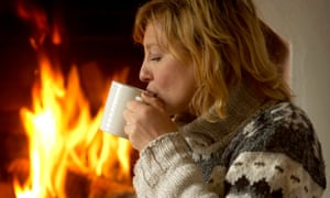 Young woman sitting in front of a fireside on a carpet and is drinking tea
