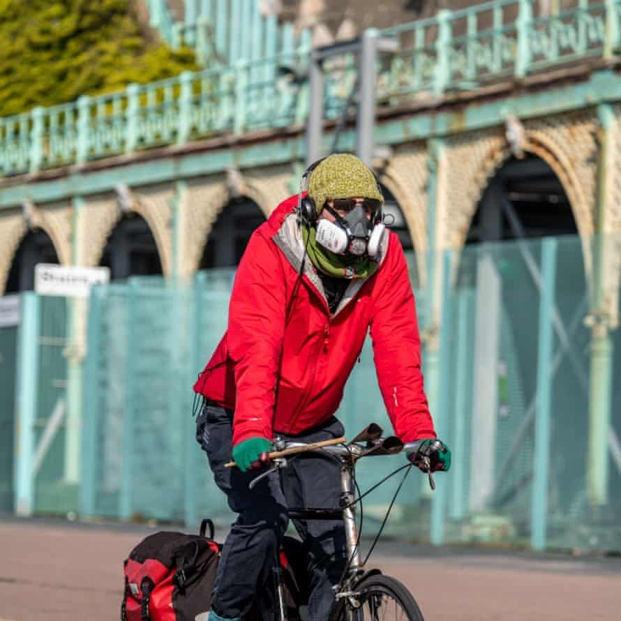 A cyclist in a protective mask cycles along Madeira Drive in Brighton.